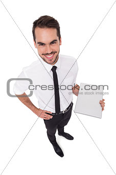 Smiling businessman standing and holding laptop