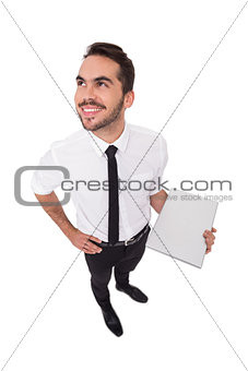 Happy businessman holding laptop and looking up