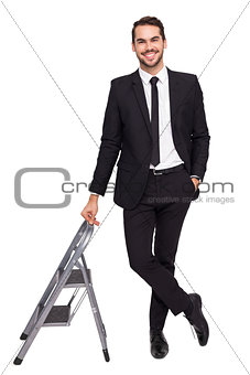 Smiling businessman leaning on stepladder