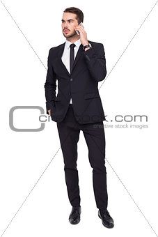 Serious businessman hand in pocket phoning