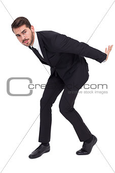 Businessman carrying something with his back and hands