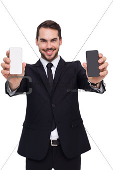 Smiling businessman showing mobile in each hand