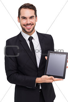 Smiling businessman showing his tablet pc