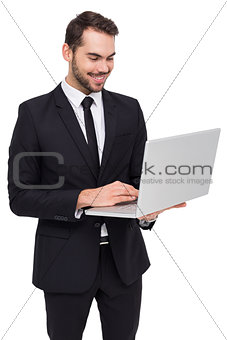 Smiling businessman standing and using laptop