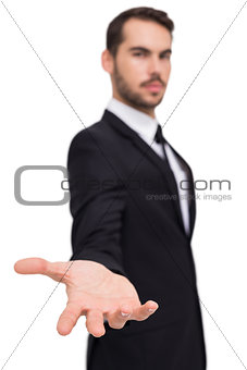 Smiling businessman offering something with his open hand