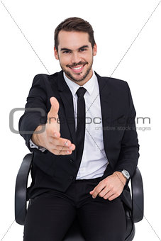 Smiling businessman on an chair office offering handshake