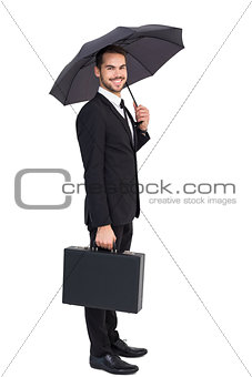 Smiling businessman under umbrella with a briefcase