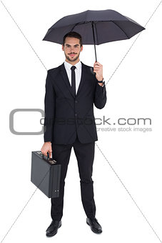 Smiling businessman under umbrella while holding briefcase