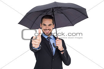 Positive businessman under umbrella with thumbs up