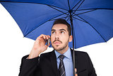 Serious businessman under umbrella phoning