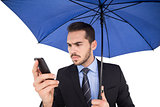 Concentrated businessman under umbrella using mobile
