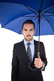 Cheerful businessman standing under umbrella