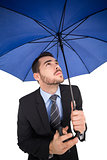 Focused businessman under umbrella looking up