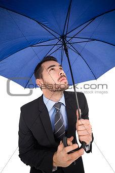 Focused businessman under umbrella looking up