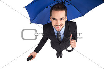 Smiling businessman under umbrella holding smartphone