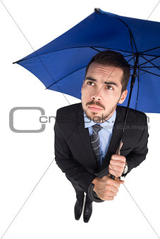 Anxious businessman under umbrella looking up