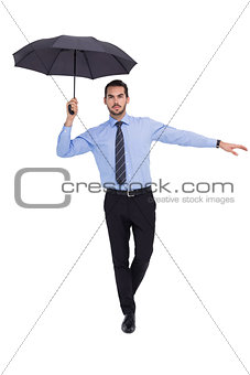 Focused businessman with umbrella balancing