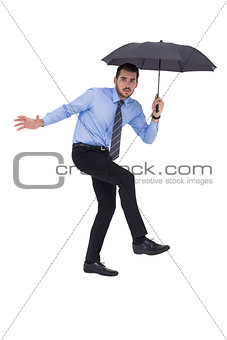 Anxious businessman under umbrella balancing