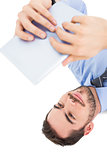 Smiling businessman lying on floor using tablet
