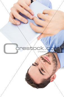 Smiling businessman lying on floor using tablet