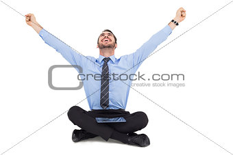 Businessman cheering with tablet sitting on floor