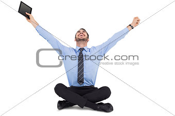 Businessman cheering and holding his tablet