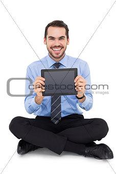 Smiling businessman showing his digital tablet