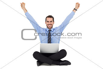 Smiling businessman sitting on the floor cheering