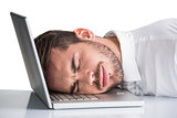 Cheerful businessman resting head on his laptop