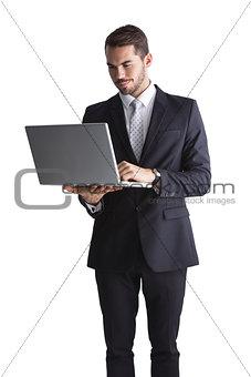 Smiling businessman standing using laptop