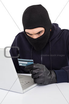 Angry hacker using laptop and credit card
