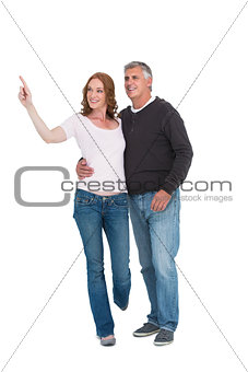 Casual couple walking and pointing