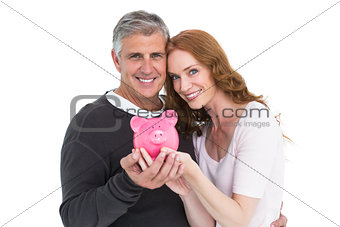Casual couple showing their piggy bank