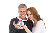 Casual couple holding small house