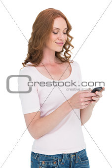 Pretty redhead sending text message