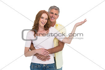 Casual couple smiling and presenting