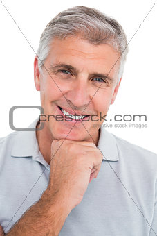 Casual man smiling with hand on chin