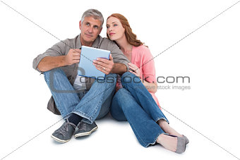 Casual couple sitting using tablet
