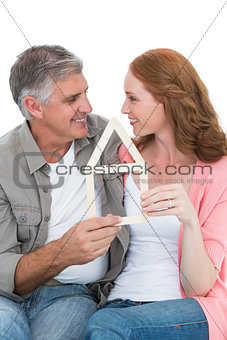Casual couple holding house outline