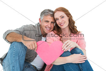 Casual couple holding pink heart