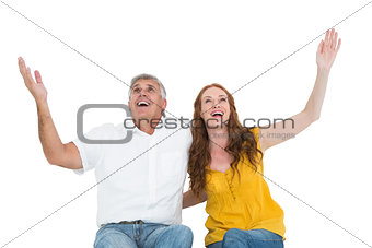 Casual couple smiling with arms raised