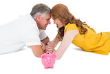 Casual couple lying on floor with piggy bank