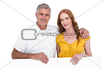 Casual couple showing a poster