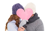 Couple in warm clothing holding heart