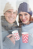Happy couple in warm clothing holding mugs