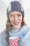 Pretty redhead in warm clothing holding mug