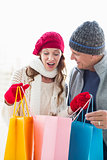 Happy couple in warm clothing opening shopping bags