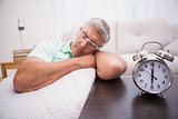 Man dozing on the couch beside alarm clock