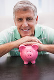 Smiling mature man with piggy bank