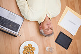Man lying on floor surrounded by various objects